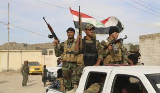 Sunni volunteer fighters parade through Khalidiya, Iraq, as they prepare to support Iraqi security forces in liberating the city of Ramadi from Islamic State militants on Oct. 10, 2015. (Associated Press)