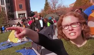 "Melissa Click, an assistant professor in the University of Missouri Department of Communication, was shown on video trying to grab a recording device from Mark Schierbecker and calling to a mob of protesters forming a human wall to ""muscle"" him out of the media ""safe space"" area. The video, uploaded by Mr. Schierbecker also showed student activists trying to intimidate Tim Tai, a student photographer. (YouTube/@Mark Schierbecker)"