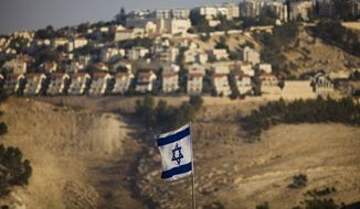 An Israeli flag is seen in front of the West Bank Jewish settlement of Maaleh Adumim on the outskirts of Jerusalem in this Sept. 7, 2009, file photo. (AP Photo/Bernat Armangue, File)