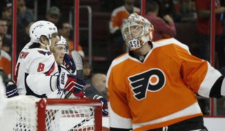 Washington Capitals' Alex Ovechkin, left, and T.J. Oshie, center, celebrate after Oshie's goal against Philadelphia Flyers' Steve Mason during the first period of an NHL hockey game Thursday, Nov. 12, 2015, in Philadelphia. (AP Photo/Matt Slocum)