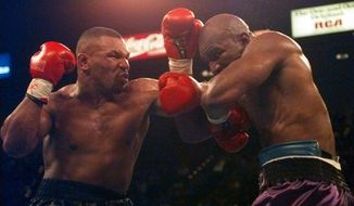 Mike Tyson and Evander Holyfield battle during their WBA Heavyweight Championship bout at the MGM Grand Garden in Las Vegas, Nev., Saturday, Nov. 9, 1996. (AP Photo/ Mark J. Terrill)