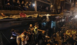 People gather near the site of a twin suicide attack in Burj al-Barajneh, southern Beirut, Lebanon, Thursday, Nov. 12, 2015 that struck a Shiite suburb killed and wounded dozens, a Lebanese official said. (AP Photo/Bilal Hussein)