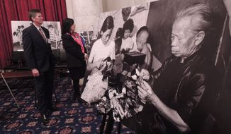 Phillip Littleton and Susan Soonkeum Cox, officials with Holt International Children's Services, stand amid the dozens of photographs depicting the lives of Vietnamese children in the 1970s at a Capitol Hill exhibit on Nov. 12, 2015. Many of the children were adopted by families in the United States. (Photo Special to The Washington Times/Douglas Wetzstein)