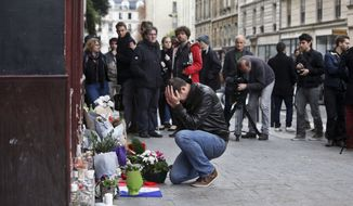 A man holds his head in his hands as he lays flowers in front of the Carillon cafe, in Paris, Saturday, Nov.14, 2015. French President Francois Hollande vowed to attack Islamic State without mercy as the jihadist group admitted responsibility Saturday for orchestrating the deadliest attacks inflicted on France since World War II. (AP Photo/Thibault Camus)