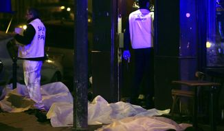 Victims lay on the pavement in a Paris restaurant, Friday, Nov. 13, 2015. Two police officials say at least 11 people have been killed in shootouts and other violence around Paris. Police have reported shootouts in at least two restaurants in Paris, and at least two explosions have been heard near the Stade de France stadium, and French media is reporting of a hostage-taking in the capital. (AP Photo/Thibault Camus)