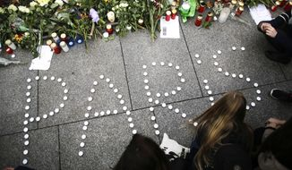 Young women have formed  the word Paris with candles to mourn for the victims killed in  Friday's attacks in Paris, France, in front of the French Embassy in Berlin, Saturday, Nov. 14, 2015. French President Francois Hollande said more than 120 people died Friday night in shootings at Paris cafes, suicide bombings near France's national stadium and a hostage-taking slaughter inside a concert hall.  (AP Photo/Markus Schreiber)