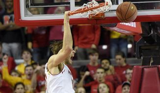 Maryland forward Jake Layman, top, dunks over Mount St. Mary's guard Elijah Long (13) during the first half of an NCAA college basketball game, Friday, Nov. 13, 2015, in College Park, Md. Maryland forward Michal Cekovsky (15) looks on. (AP Photo/Nick Wass)