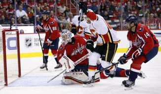 Calgary Flames right wing Michael Frolik (67), from the Czech Republic, celebrates his goal past Washington Capitals goalie Philipp Grubauer (31), from Germany, in the second period of an NHL hockey game, Friday, Nov. 13, 2015, in Washington. (AP Photo/Alex Brandon)