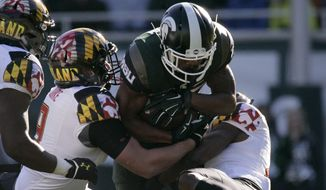 Michigan State's Madre London, center, is stopped by Maryland's Tyler Burke, left, and Sean Davis, right, during the second quarter of an NCAA college football game, Saturday, Nov. 14, 2015, in East Lansing, Mich. (AP Photo/Al Goldis)