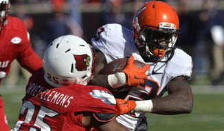 Louisville safety Josh Harvey-Clemons (25) wraps up Virginia wide receiver Olamide Zaccheaus (33) during the first half of an NCAA college football game Saturday, Nov. 14, 2015, in Louisville, Ky. (AP Photo/Timothy D. Easley)