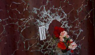 Flowers are put in a window shattered by a bullet as a forensic marker sits next to the impact as people pay their respect to the victims at the site of the attacks on restaurant Le Petit Cambodge (Little Cambodia) and the Carillon Hotel on the first of three days of national mourning in Paris, Sunday, Nov. 15, 2015. Thousands of French troops deployed around Paris on Sunday and tourist sites stood shuttered in one of the most visited cities on Earth while investigators questioned the relatives of a suspected suicide bomber involved in the country's deadliest violence since World War II. (AP Photo/Peter Dejong)