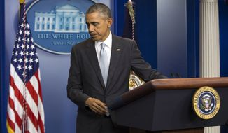 """President Barack Obama walks from the podium after speaking about attacks in Paris from the briefing room of the White House, on Friday, Nov. 13, 2015, in Washington.  Obama is calling the attacks on Paris an """"outrageous attempt to terrorize innocent civilians"""" and vows to do whatever it takes to help bring the perpetrators to justice. (AP Photo/Evan Vucci)"""
