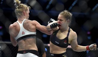 Holly Holm, left, and Ronda Rousey exchange their punches during their UFC 193 bantamweight title fight in Melbourne, Australia, Sunday, Nov. 15, 2015. Holm pulled off a stunning upset victory over Rousey in the fight, knocking out the women's bantamweight champion in the second round with a powerful kick to the head Sunday. (AP Photo/Andy Brownbill)