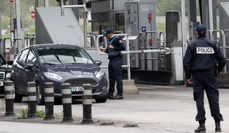 French police officers check vehicles leaving France at the border crossing between France and Spain in Biriatou on Saturday, Nov. 14, 2015. (Associated Press)