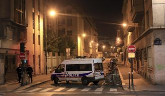 Police officers stand in a street next to Le Carillon, a bar-cafe where people were killed and several gravely injured, according to the prosecutor, in Paris, Saturday, Nov. 14, 2015. A series of attacks targeting young concert-goers, soccer fans and Parisians enjoying a Friday night out at popular nightspots killed over 100 people in the deadliest violence to strike France since World War II. (AP Photo/Thibault Camus)