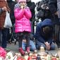 People mourn for the victims of the deadly attacks in Paris, outside the French embassy in Warsaw, Poland, Saturday, Nov. 14, 2015. French President Francois Hollande said more than 120 people died Friday night in shootings at Paris cafes, suicide bombings near France's national stadium and a hostage-taking slaughter inside a concert hall. (AP Photo/Alik Keplicz)