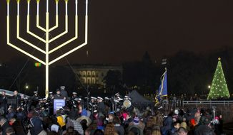 """FILE - In this Sunday, Dec. 9, 2012 file photo, with the White House in the background and the National Christmas Tree at right, people stand for a song at the end of the lighting of the National Hanukkah Menorah, during an event sponsored by the American Friends of Lubavitch, on The Ellipse in Washington marking the second night of the Jewish holiday Hanukkah. Starbucks' late 2015 cups, holiday drinks and merchandise put it in the legion of companies that have seized on the sales potential of the Christmas season, while preferring to glaze over religiosity in a country that is increasingly pluralistic, said Leigh Schmidt, author of """"Consumer Rites: The Buying and Selling of the American Holidays."""" (AP Photo/Jacquelyn Martin)"""