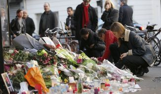 People place flowers and candles in front of the restaurant on Rue de Charonne, Paris, Sunday, Nov. 15, 2015, where attacks took place on Friday. The Islamic State group claimed responsibility for Friday's attacks on a stadium, a concert hall and Paris cafes that left more than 120 people dead and over 350 wounded. (AP Photo/Frank Augstein)