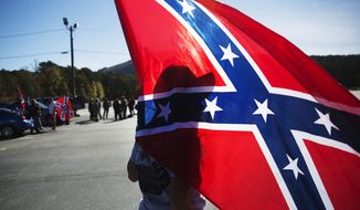 Tara Brandau, of Lake City, Fla., casts a shadow against a confederate flag as supporters gather before hiking up Stone Mountain during a rally in Georgia on Nov. 14, 2015. (Associated Press) **FILE**
