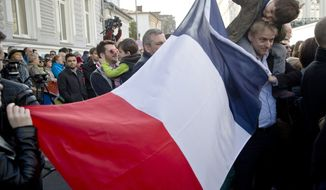People hold a French flag while waiting to pay respects to victims of the terrorist attacks at the French Embassy in Bucharest, Romania, Sunday, Nov. 15, 2015. Multiple terrorist attacks across Paris on Friday night have left more than one hundred dead and many more injured. (AP Photo/Vadim Ghirda)
