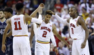 Maryland guard Melo Trimble (2) celebrates with teammates Jared Nickens, left, and Rasheed Sulaimon after scoring to tie the game in the second half of an NCAA college basketball game against Georgetown, Tuesday, Nov. 17, 2015, in College Park, Md. Maryland won 75-71. (AP Photo/Patrick Semansky)