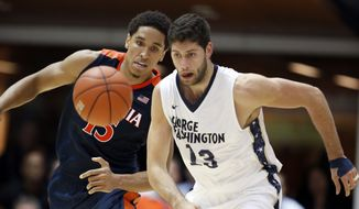 Virginia guard Malcolm Brogdon (15) and George Washington guard Patricio Garino (13) chase after the loose ball during the first half of an NCAA college basketball game, Monday, Nov. 16, 2015, in Washington. George Washington won 73-68. (AP Photo/Alex Brandon)
