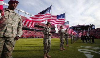 Servicemen hold American flags on the field during an NFL football game between the Denver Broncos and the Kansas City Chiefs. (AP Photo/Jack Dempsey)