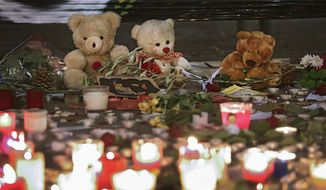 Teddy bears are displayed  to pay tribute to the victims of the terror attacks in Paris, Monday, Nov. 16, 2015, in Nice, southeastern France. France is urging its European partners to move swiftly to boost intelligence sharing, fight arms trafficking and terror financing, and strengthen border security in the wake of the Paris attacks. (AP Photo/Lionel Cironneau)