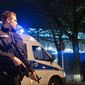 A police officer carries a submachine gun outside the HDI-Arena in Hanover, Germany, Tuesday, Nov. 17, 2015. The international friendly between Germany and Holland match was called off at short notice and the stadium was evacuated. (Julian Stratenschulte/dpa via AP)