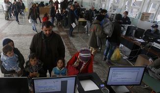 Migrants family wait to register with the police in a refugee center in the southern Serbian town of Presevo, Monday, Nov. 16, 2015. Refugees fleeing war by the tens of thousands fear the Paris attacks could prompt Europe to close its doors, especially after police said a Syrian passport found next to one attacker's body suggested its owner passed through Greece into the European Union and on through Macedonia and Serbia last month. (AP Photo/Darko Vojinovic)