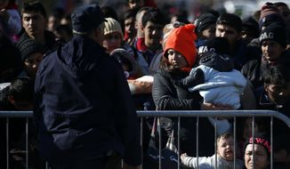 Migrants wait to register with the police at a refugee center in the southern Serbian town of Presevo, Monday, Nov. 16, 2015. Refugees fleeing war by the tens of thousands fear the Paris attacks could prompt Europe to close its doors, especially after police said a Syrian passport found next to one attacker's body suggested its owner passed through Greece into the European Union and on through Macedonia and Serbia last month. (AP Photo/Darko Vojinovic) ** FILE **