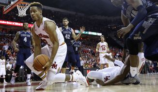 Maryland guard Melo Trimble, left, tries to keep the ball in bounds in the second half of an NCAA college basketball game against Georgetown, Tuesday, Nov. 17, 2015, in College Park, Md. Maryland won 75-71. (AP Photo/Patrick Semansky)