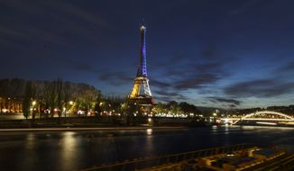 With the River Seine in the foreground the illuminated Eiffel Tower in the French national colors red, white and blue in honor of the victims of the terrorist attacks last Friday, and Seine river are seen in Paris, Wednesday, Nov. 18, 2015. A woman wearing an explosive suicide vest blew herself up Wednesday as heavily armed police tried to storm a suburban Paris apartment where the suspected mastermind of last week's attacks was believed to be holed up, police said. (AP Photo/Daniel Ochoa de Olza)