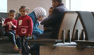 A Syrian refugee family sits at the immigration office of Incheon International Airport in Incheon, South Korea, Wednesday, Nov. 18, 2015. South Korea's spy service told lawmakers on Wednesday about 200 Syrians fleeing war have arrived by airplane in South Korea, but the government has yet to decide whether to grant refugee status to any of them.(Shin Jun-hee/Yonhap via AP) KOREA OUT