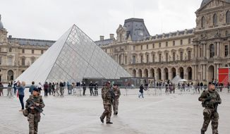 Soldiers patrol in the courtyard of the Louvre museum in Paris in 2015. (Associated Press photographs) ** FILE **