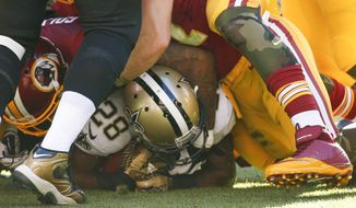 New Orleans Saints running back C.J. Spiller (28) is crushed on the Washington Redskins defense during the first half of an NFL football game in Landover, Md., Sunday, Nov. 15, 2015. (AP Photo/Alex Brandon)