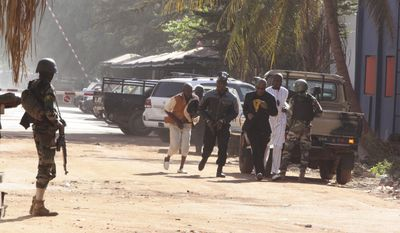 People run to flee from the Radisson Blu Hotel in Bamako, Mali, Friday, Nov. 20, 2015. The company that runs the Radisson Blu Hotel in Mali's capital says assailants have takenhostages in a brazen assault involving grenades. (AP Photo/Harouna Traore)