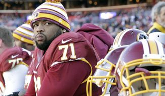 In this photo taken Dec. 7, 2014, Washington Redskins tackle Trent Williams (71) watches the action from the bench during the first half of an NFL football game against the St. Louis Rams in Landover, Md. The Redskins are 0-4 on the road this season, part of an eight-game losing streak away from home that dates to last season. In contrast, they're 4-1 at home this season, including four victories in a row.  (AP Photo/Mark Tenally)