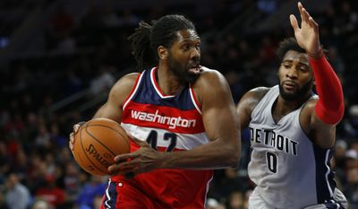 Washington Wizards forward Nene (42) drives on Detroit Pistons center Andre Drummond (0) in the second half of an NBA basketball game Saturday, Nov. 21, 2015 in Auburn Hills, Mich. (AP Photo/Paul Sancya)