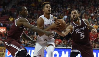 Maryland's Melo Trimble drives between Rider's Zedric Sadler, left, and Teddy Okereafor during the first half of an NCAA college basketball game Friday, Nov. 20, 2015, in College Park, Md. (AP Photo/Gail Burton)