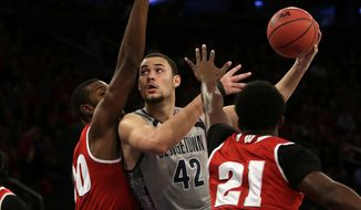 Georgetown center Bradley Hayes, center, shoots between Wisconsin guard T.J. Schlundt, left, and forward Khalil Iverson, right, during the first half of an NCAA college basketball game at Madison Square Garden on Friday, Nov. 20, 2015, in New York. (AP Photo/Adam Hunger)