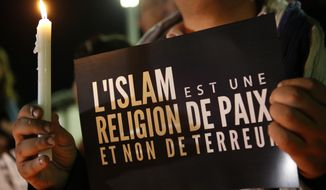 "A Moroccan Muslim man holds a banner witch read  ""Islam is a religion of peace and not terror "" as people gather in solidarity with french people one week after terror attacks in Rabat, Morocco, Friday , Nov. 20, 2015. French President Francois Hollande will preside over a national ceremony on Nov. 27 honoring the victims of the deadliest attacks on France in decades. (AP Photo/Abdeljalil Bounhar)"