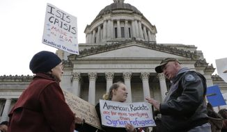 Protesters on opposing sides of the Syrian refugee resettlement issue rally in front of the state Capitol in Olympia, Wash., Friday, Nov. 20, 2015. Washington Gov. Jay Inslee has said the state will welcome refugees and has criticized other governors who have threatened to stop accepting them following last week's terror attacks in Paris. (AP Photo/Rachel La Corte)