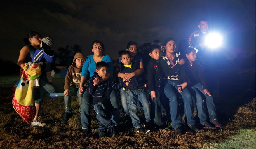 A group of immigrants from Honduras and El Salvador is stopped in Granjeno, Texas, after crossing the U.S.-Mexico border illegally. (Associated Press)