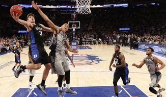 Duke guard Grayson Allen (3) becomes entangled with Georgetown forward Trey Mourning (33) while going for a layup in the second half of an NCAA college basketball game at Madison Square Garden in New York, Sunday, Nov. 22, 2015. Duke defeated Georgetown 86-84. (AP Photo/Kathy Willens)