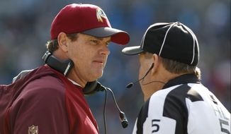 Washington Redskins head coach Jay Gruden, left, talks with head linesman John McGrath, right, in the first half of an NFL football game against the Carolina Panthers in Charlotte, N.C., Sunday, Nov. 22, 2015. (AP Photo/Bob Leverone)