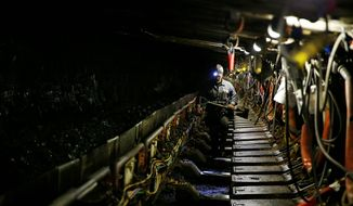 Cory Chanze, shieldman for the Ohio County Coal Company, surveys the longwall operation inside the Ohio County mine in Dallas, West Virginia. Miners are sticking to their preference for such underground work despite the Obama White House attempting to transition them into other lines of work. (Jared Wickerham/Special to the Washington Times)