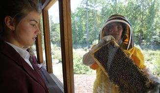 Sarah Myers, right, a manager at the Bayer North American Bee Care Center, shows a tray of bees to St. Thomas More Academy student Maria Pompi, left, during a tour of the center in Research Triangle Park, N.C., Tuesday, Sept. 15, 2015. (AP Photo/Ted Richardson) ** FILE **