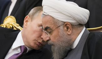Russian President Vladimir Putin, left, speaks to Iran's President Hassan Rouhani as they attend a signing ceremony during the Gas Exporting Countries Forum (GECF) in Tehran, Iran, Monday, Nov. 23, 2015. The meeting of the Gas Exporting Countries Forum (GECF) bring major producers such as Russia, Qatar and Algeria to Iran, which itself is the world's third largest producer after the U.S. and Russia. (AP Photo/Alexander Zemlianichenko)