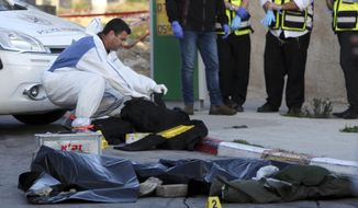 An Israeli policeman collects evidence next to a body of a Palestinian attacker at a West Bank petrol station near Jerusalem, Monday, Nov. 23, 2015. A Palestinian stabbed an Israeli man to death before he was shot dead by security forces. (AP Photo/Mahmoud Illean)